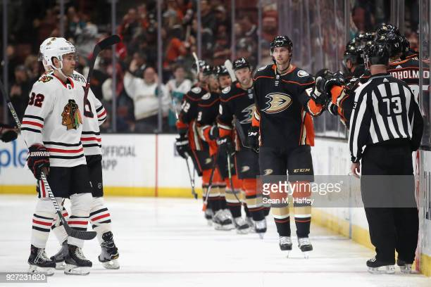 Marcus Pettersson of the Anaheim Ducks is congratulated at the bench after scoring a goal as Jordan Oesterle of the Chicago Blackhawks looks on...
