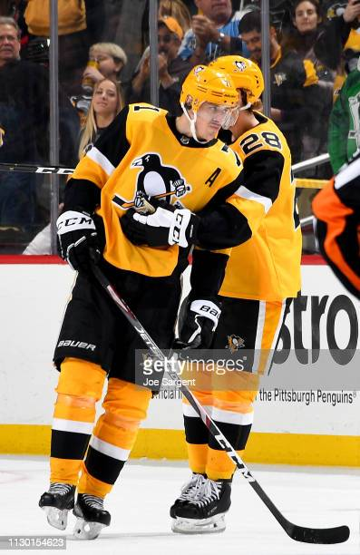 Marcus Pettersson of the Pittsburgh Penguins celebrates with Evgeni Malkin of the Pittsburgh Penguins after recording his 1000th NHL point against...