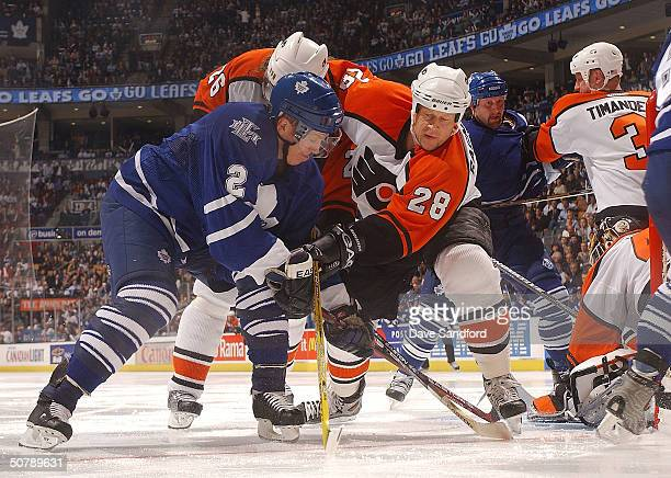 Marcus Ragnarsson of the Philadelphia Flyers battles for position with Brian Leetch of the Toronto Maple Leafs as the puck is covered up during Game...