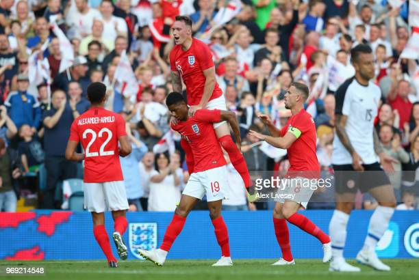 Marcus Rashford of England celebrates with Phil Jones Jordan Henderson and Trent AlexanderArnold of England during the International Friendly match...