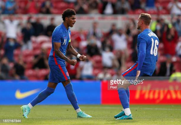 Marcus Rashford of England celebrates with team mate Jordan Henderson after scoring their side's first goal from the penalty spot during the...