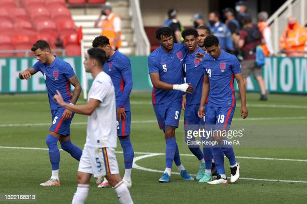 Marcus Rashford of England celebrates with team mates Tyrone Mings and Jude Bellingham after scoring their side's first goal from the penalty spot...
