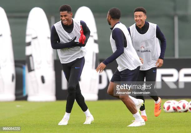 Marcus Rashford of England holds a toy chicken during a drill with Raheem Sterling of England and Jesse Lingard of England during the England...