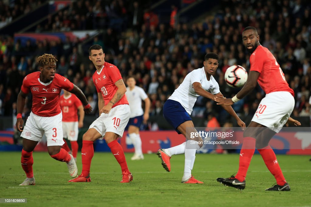 Marcus Rashford of England shoots past Johan Djourou of Switzerland (R) during the International Friendly match between England and Switzerland at The King Power Stadium on September 11, 2018 in Leicester, England.