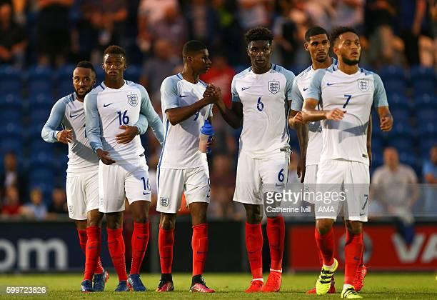Marcus Rashford of England U21 is congratulated by Kortney Hause of England U21 as he walks off with team mates Nathan Redmond Demarai Gray Ruben...