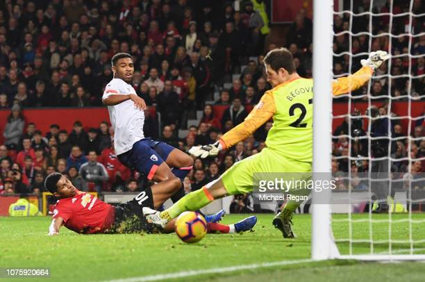 Marcus Rashford of Manchester United beats Jordon Ibe and Asmir Begovic of AFC Bournemouth as he scores his team's third goal during the Premier...