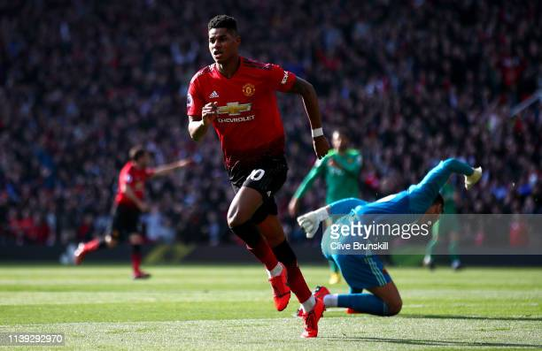 Marcus Rashford of Manchester United celebrates after scoring his team's first goal as Ben Foster of Watford reacts during the Premier League match...