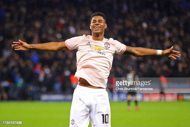 Marcus Rashford of Manchester United celebrates scoring his side's third goal from the penalty spot during the UEFA Champions League Round of 16...