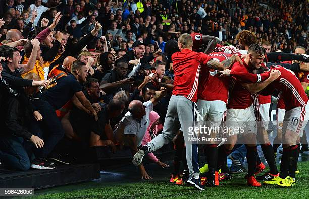 Marcus Rashford of Manchester United celebrates scoring his sides first goal with team mates and fans during the Premier League match between Hull...