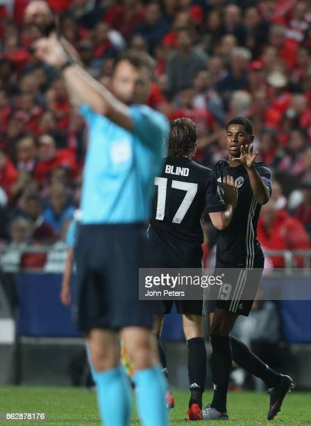 Marcus Rashford of Manchester United celebrates scoring their first goal as referee Felix Zwayer points at his watch to show the ball crossed the...