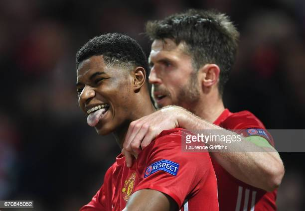 Marcus Rashford of Manchester United celebrates with team mate Michael Carrick as he scores their second goal during the UEFA Europa League quarter...