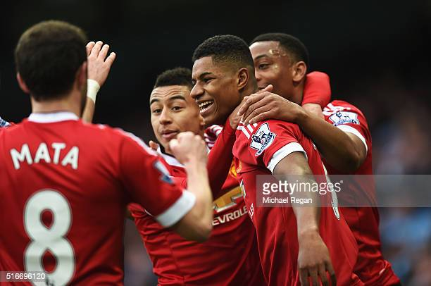 Marcus Rashford of Manchester United celebrates with team mates as he scores their first goal during the Barclays Premier League match between...