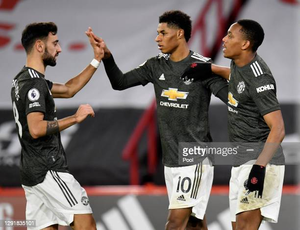 Marcus Rashford of Manchester United celebrates with team mates Bruno Fernandes and Anthony Martial after scoring their sides third goal during the...