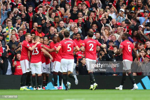 Marcus Rashford of Manchester United celebrates with teammates after scoring his team's first goal during the Premier League match between Manchester...