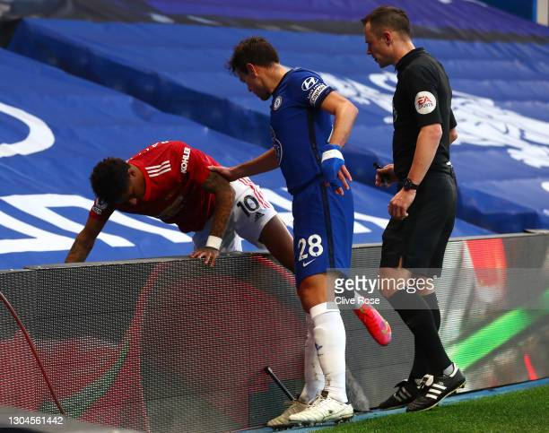 Marcus Rashford of Manchester United collides with the LED boards as Cesar Azpilicueta of Chelsea and Match Referee, Stuart Attwell help during the...