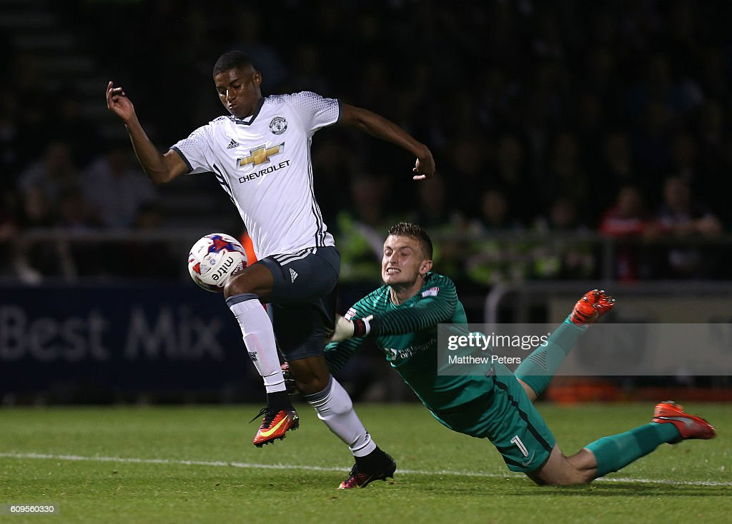 Marcus Rashford of Manchester United goes past Adam Smith of Northampton to score his team's third goal during the EFL Cup Third Round match between Northampton Town and Manchester United at Sixfields on September 21, 2016 in Northampton, England.