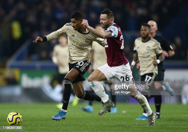 Marcus Rashford of Manchester United holds off a challenge by Phil Bardsley of Burnley FC during the Premier League match between Burnley FC and...