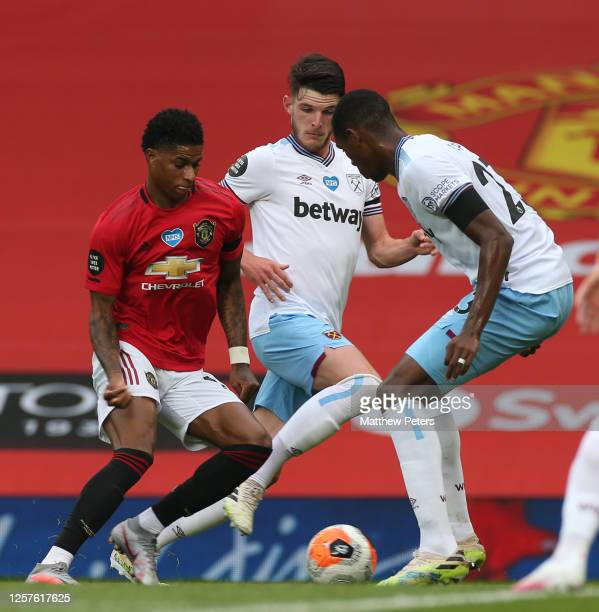 Marcus Rashford of Manchester United in action with Declan Rice and Issa Diop of West Ham United during the Premier League match between Manchester...