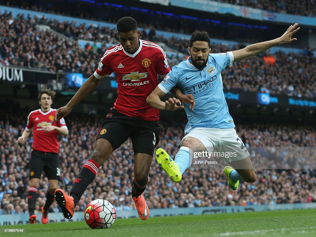 Marcus Rashford of Manchester United in action with Gael Clichy of Manchester City during the Barclays Premier League match between Manchester City and Manchester United at Etihad Stadium on March 20, 2016 in Manchester, United Kingdom.