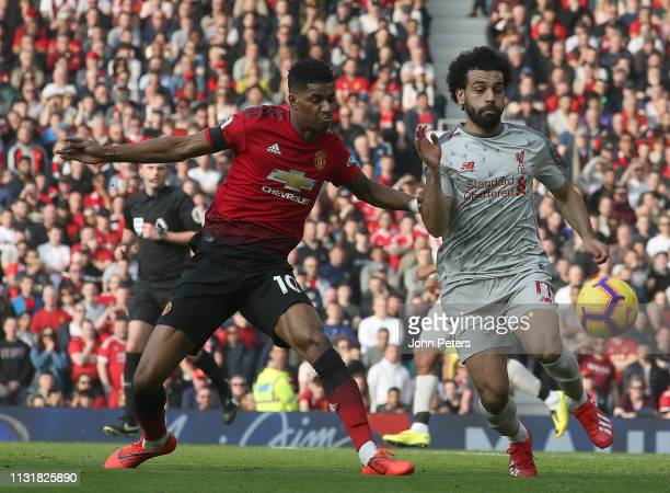 Marcus Rashford of Manchester United in action with Mohamed Salah of Liverpool during the Premier League match between Manchester United and...