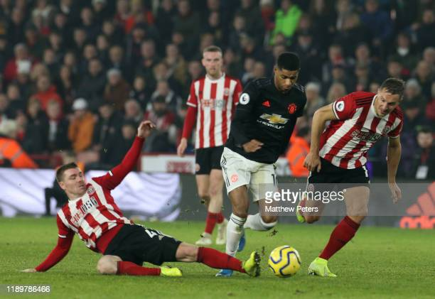 Marcus Rashford of Manchester United in action with Phil Jagielka and John Fleck of Sheffield United during the Premier League match between...