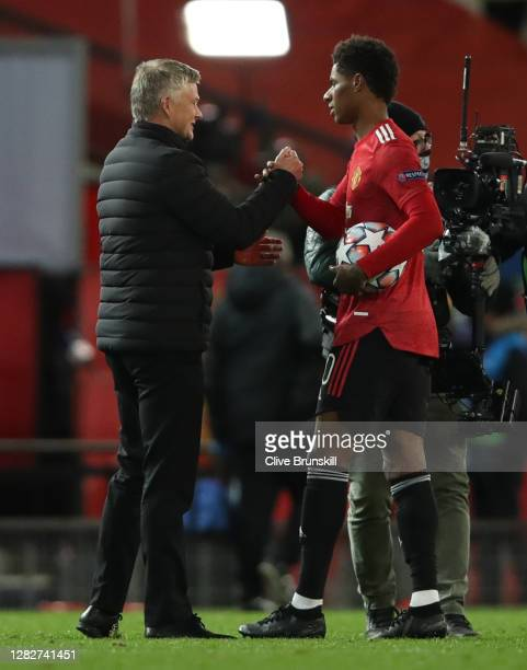 Marcus Rashford of Manchester United interacts with Ole Gunnar Solskjaer, Manager of Manchester United whilst holding the match ball after scoring a...