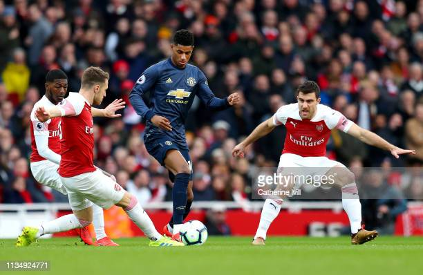 Marcus Rashford of Manchester United is challenged by Aaron Ramsey of Arsenal during the Premier League match between Arsenal FC and Manchester...