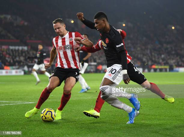 Marcus Rashford of Manchester United is challenged by Phil Jagielka of Sheffield United during the Premier League match between Sheffield United and...