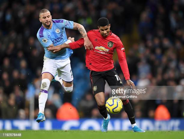 Marcus Rashford of Manchester United is held back by Kyle Walker of Manchester City during the Premier League match between Manchester City and...