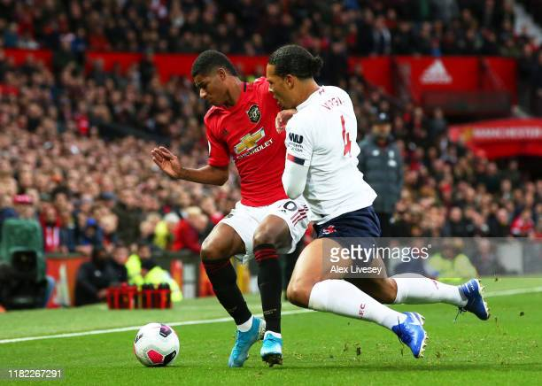 Marcus Rashford of Manchester United is tackled by Virgil van Dijk of Liverpool during the Premier League match between Manchester United and...