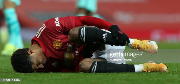 Marcus Rashford of Manchester United lies injured during the Emirates FA Cup Fourth Round match between Manchester United and Liverpool at Old...