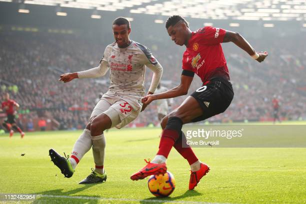 Marcus Rashford of Manchester United looks to cross the ball under pressure from Joel Matip of Liverpool during the Premier League match between...