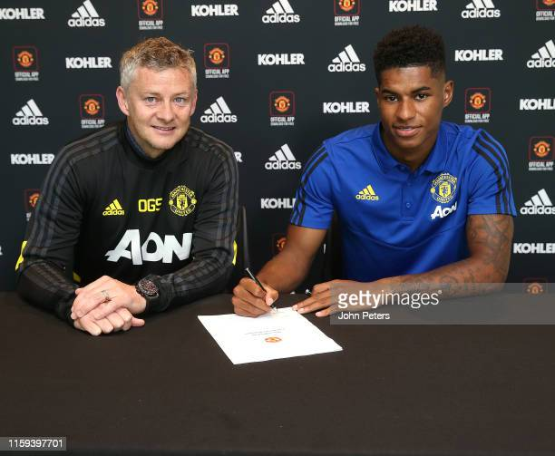 Marcus Rashford of Manchester United poses with Manager Ole Gunnar Solskjaer after signing a contract extension at the club at Aon Training Complex...