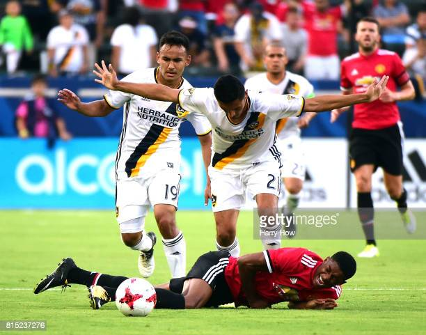 Marcus Rashford of Manchester United reacts as he loses the ball to Hugo Arellano and Jaime Villarreal of Los Angeles Galaxy during the first half at...