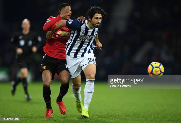 Marcus Rashford of Manchester United reacts to being caught in the face by Ahmed ElSayed Hegazi of West Bromwich Albion as he runs with the ball...