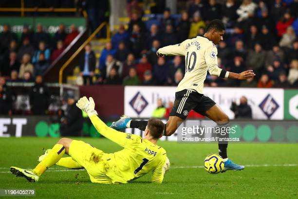 Marcus Rashford of Manchester United rounds Nick Pope of Burnley before scoring his side's second goal during the Premier League match between...