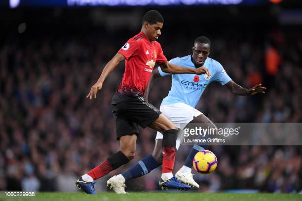 Marcus Rashford of Manchester United runs with the ball under pressure from Benjamin Mendy of Manchester City during the Premier League match between...