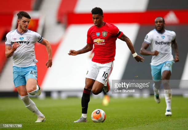 Marcus Rashford of Manchester United runs with the ball whilst under pressure from Declan Rice of West Ham United during the Premier League match...