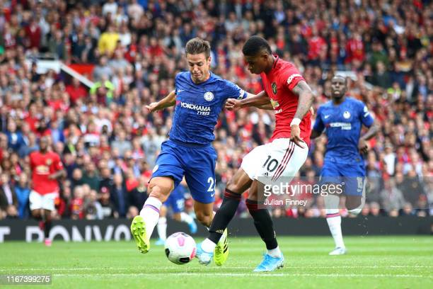 Marcus Rashford of Manchester United scores his team's third goal under pressure from Cesar Azpilicueta of Chelsea during the Premier League match...