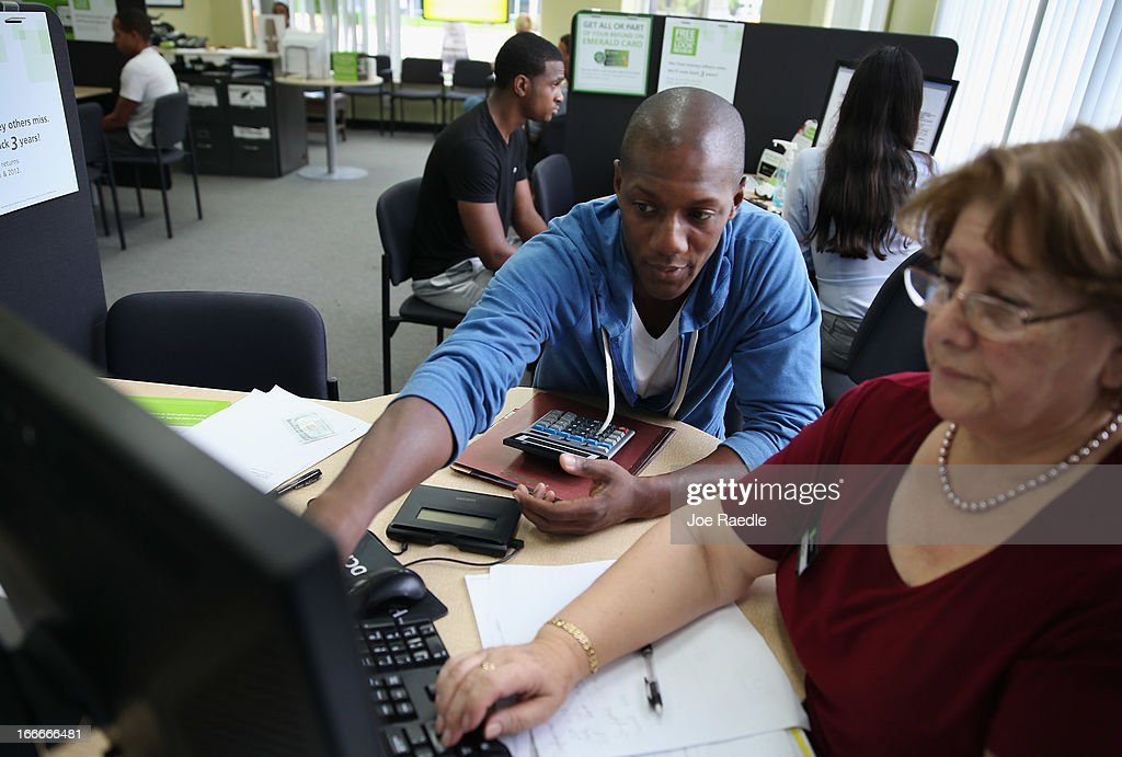Marcus Sebastian (L) sits with Flor Reyes, tax associate, as he does his taxes at the H&R Block office on April 15, 2013 in Miami Beach, Florida. With the U.S. tax deadline of midnight April 15 rapidly approaching, last-minute filers are rushing to get their returns done.