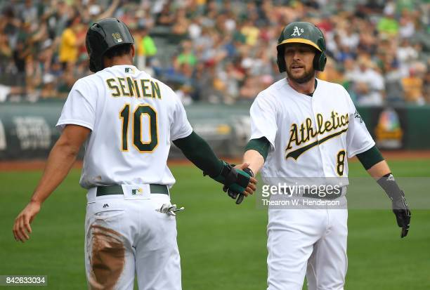 Marcus Semien and Jed Lowrie of the Oakland Athletics celebrate after they scored on a bases loaded double hit by Khris Davis against the Los Angeles...