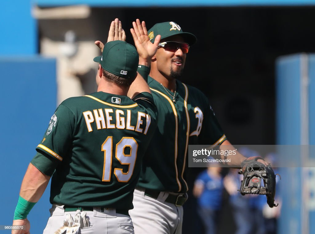 Marcus Semien #10 of the Oakland Athletics celebrates their victory with Josh Phegley #19 during MLB game action against the Toronto Blue Jays at Rogers Centre on May 20, 2018 in Toronto, Canada.