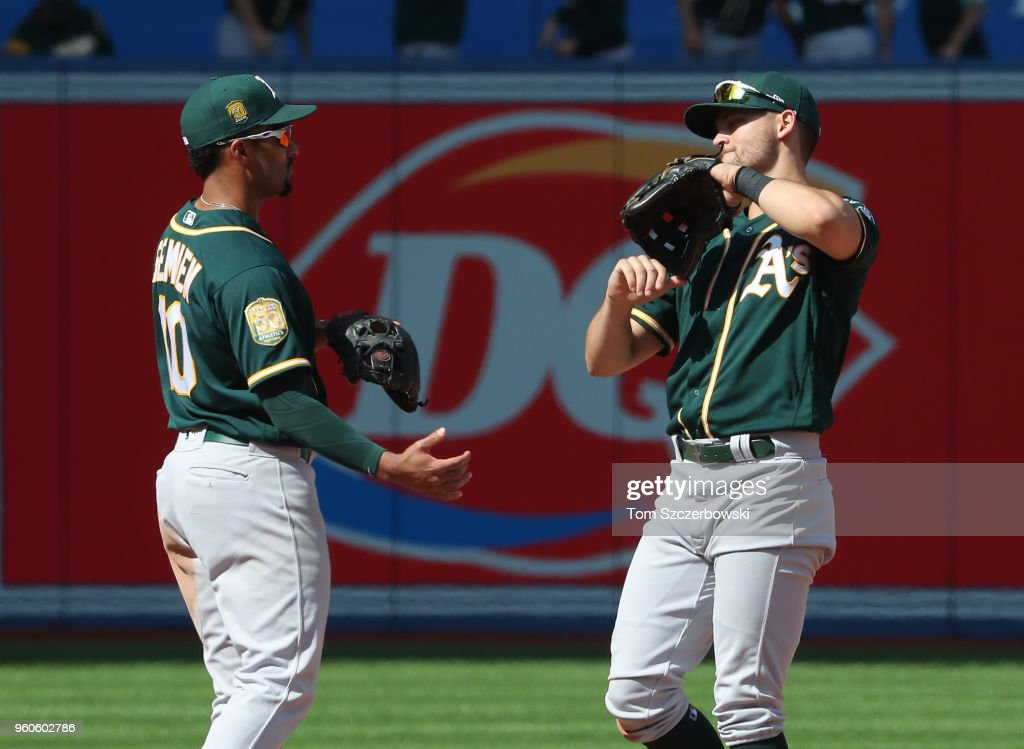 Marcus Semien #10 of the Oakland Athletics celebrates their victory with Chad Pinder #18 during MLB game action against the Toronto Blue Jays at Rogers Centre on May 20, 2018 in Toronto, Canada.