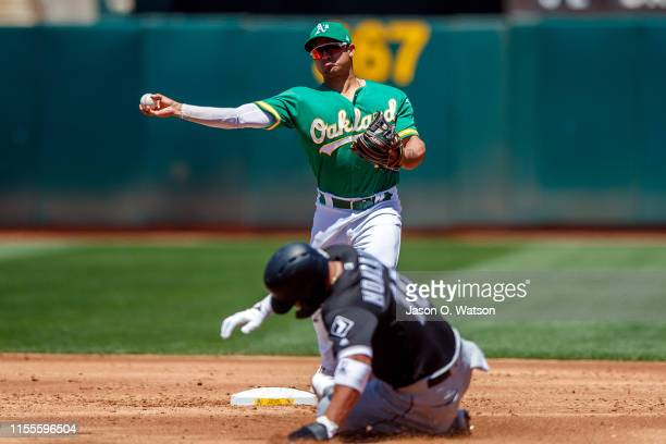 Marcus Semien of the Oakland Athletics completes a double play over Yoan Moncada of the Chicago White Sox during the third inning at the RingCentral...