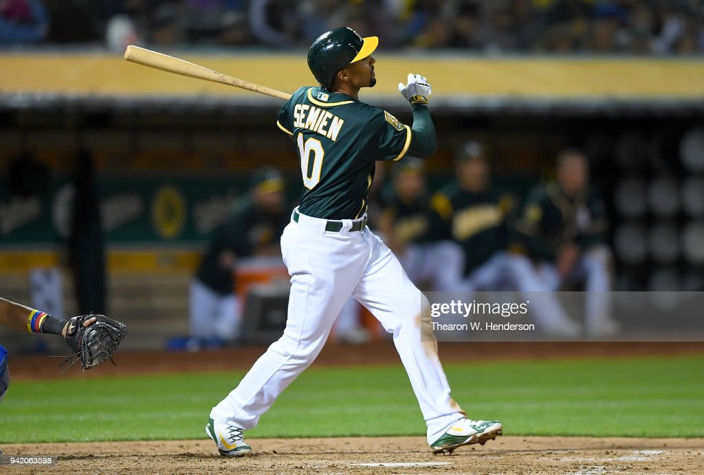 Marcus Semien #10 of the Oakland Athletics hits a sacrifice fly scoring Chad Pinder #18 against the Texas Rangers in the bottom of the fourth inning at the Oakland Alameda Coliseum on April 4, 2018 in Oakland, California.