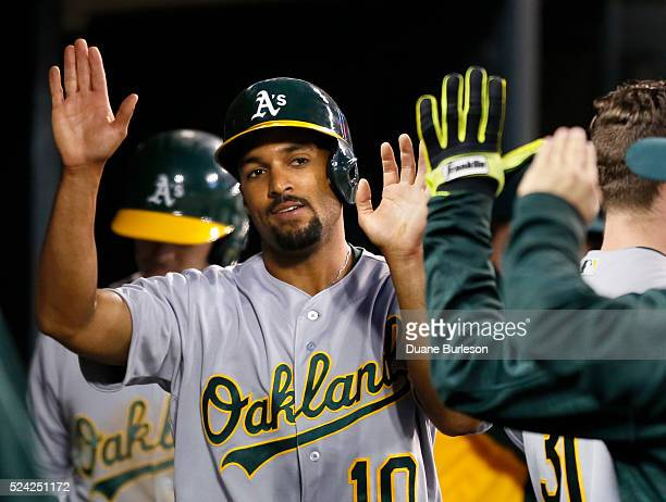 Marcus Semien of the Oakland Athletics is congratulated after scoring against the Detroit Tigers on a single by Billy Burns of the Oakland Athletics...