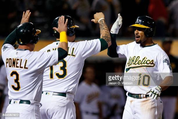 Marcus Semien of the Oakland Athletics is congratulated by Bruce Maxwell and Boog Powell after hitting a grand slam home run against the Houston...