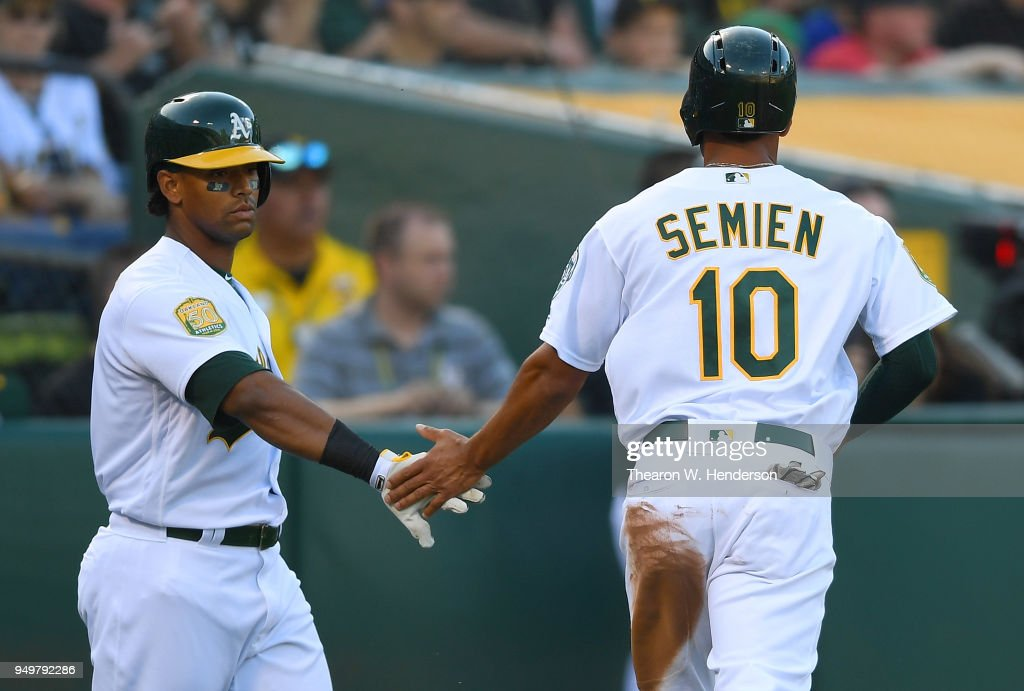 Marcus Semien #10 of the Oakland Athletics is congratulated by Khris Davis #2 after Semien scored against the Boston Red Sox in the bottom of the first inning at the Oakland Alameda Coliseum on April 21, 2018 in Oakland, California.