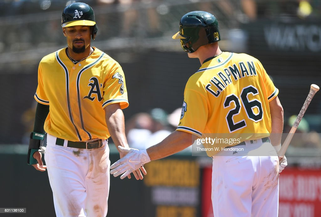 Marcus Semien #10 of the Oakland Athletics is congratulated by Matt Chapman #26 after Semien scored against the Baltimore Orioles in the bottom of the fourth inning at Oakland Alameda Coliseum on August 13, 2017 in Oakland, California.