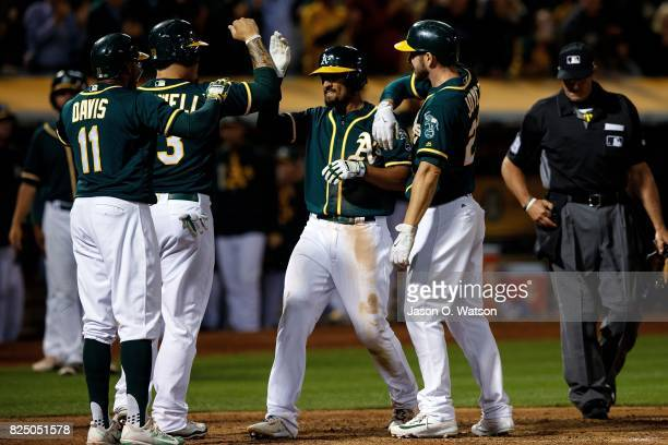 Marcus Semien of the Oakland Athletics is congratulated by Rajai Davis Bruce Maxwell and Matt Joyce after hitting a grand slam home run against the...